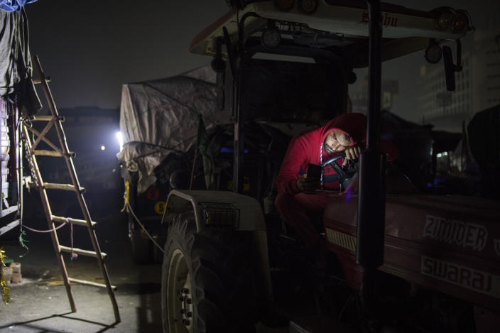 """Farmer Brijender Singh, 24, looks at his mobile phone while sitting on his tractor parked on a highway during a protest at the Delhi-Haryana state border, India, Wednesday, Dec. 2, 2020. The convoy of trucks, trailers and tractors stretches for at least three kilometers (1.8 miles) with farmers protesting new farm laws. Their rallying call is """"Inquilab Zindabad"""" (""""Long live the revolution""""). (AP Photo/Altaf Qadri)"""