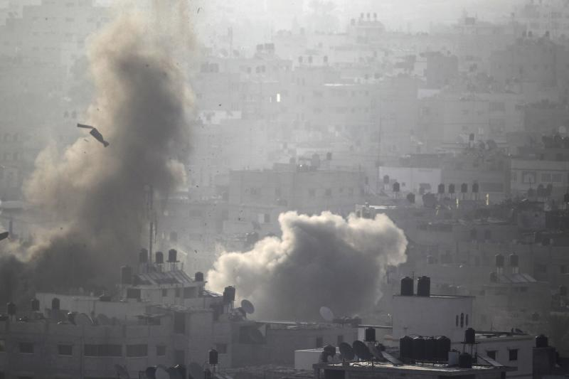 Smoke rises following what witnesses said were Israeli air strikes in Gaza August 26, 2014. Israeli air strikes launched before dawn on Tuesday killed two Palestinians and destroyed much of one of Gaza's tallest apartment and office buildings, setting off huge explosions and wounding 20 people, Palestinian health officials said. Israel had no immediate comment on the attacks that took place as Egyptian mediators stepped up efforts to achieve an elusive ceasefire to end seven weeks of fighting. Israel launched an offensive on July 8, with the declared aim of ending rocket fire into its territory. REUTERS/Ahmed Zakot (GAZA - Tags: POLITICS CIVIL UNREST)