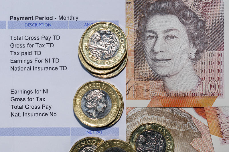 London, UK: July 25, 2018: Pay Slip with British one pound coins with a ten pound note background indicating a monthly payment in a horizontal format.