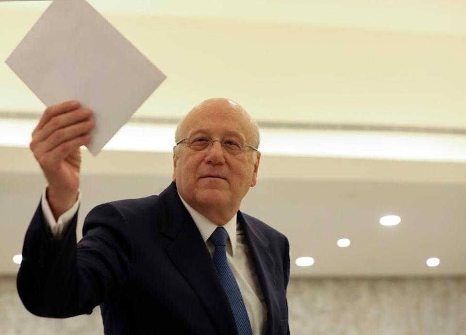 Lebanon's prime minister Najib Mikati holds the cabinet list after meeting with the country's president Michel Aoun at the presidential palace in Baabda, Lebanon (Reuters)