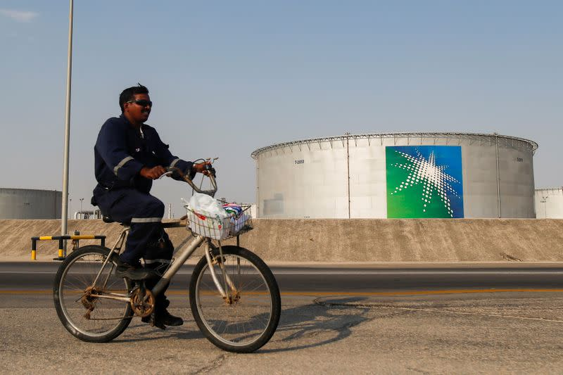 An employee rides a bicycle next to oil tanks at Saudi Aramco oil facility in Abqaiq