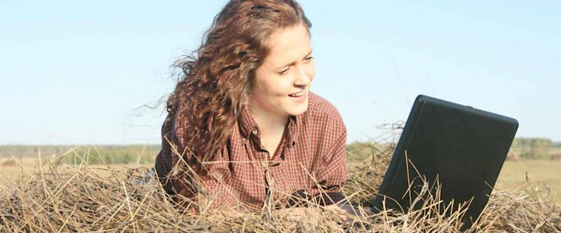 Country ginger girl typing on laptop lying on haystack
