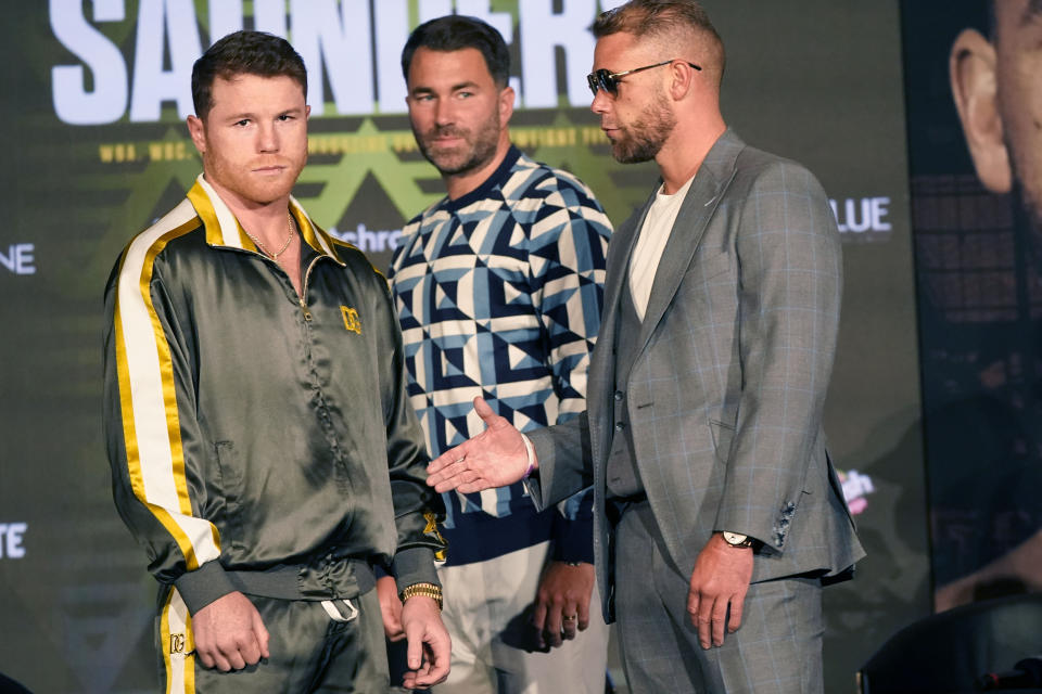 Canelo Alvarez of Mexico, left, turns away as Billy Joe Saunders of Great Britain, right, offer to shake hands with promoter Eddie Hearn looking on during a pre-fight news conference, Thursday, May 6, 2021, in Arlington, Texas. Alvarez and Saunders fight on Saturday, May 8, 2021, for the unified super middleweight world championship. (AP Photo/LM Otero)