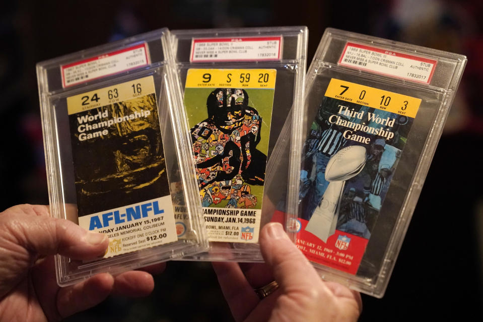 Don Crisman holds tickets from the first three Super Bowls, Wednesday, Jan. 27, 2021, in Kennebunk, Maine. Crisman is one of three fans who have attended every Super Bowl. (AP Photo/Robert F. Bukaty)
