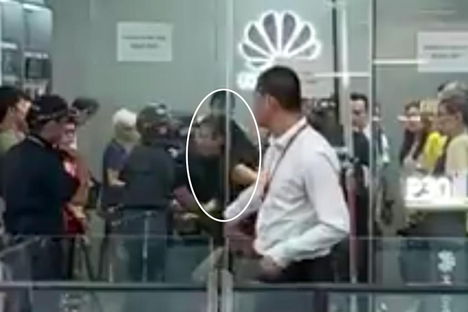 Ng Puay Chin seen being arrested at the Huawei shop on 26 July. (PHOTO: YouTube screengrab)
