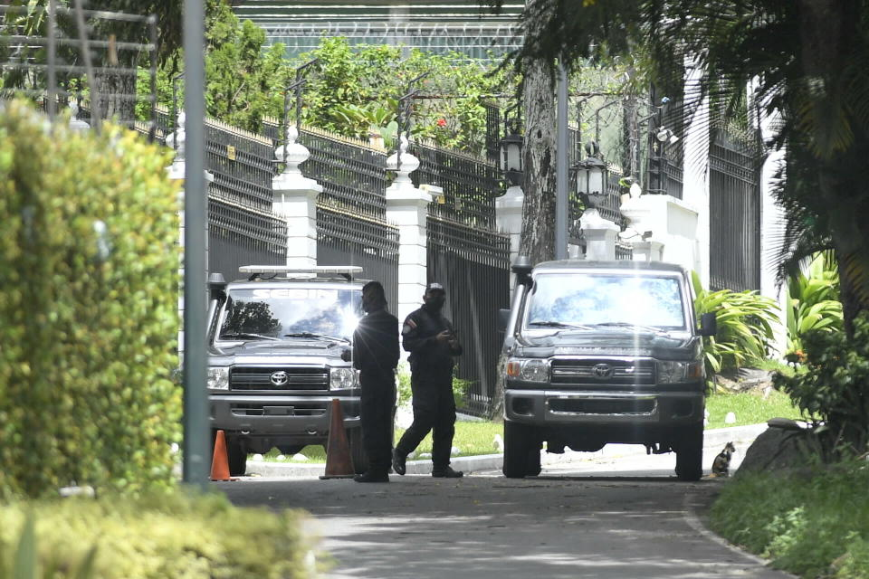 Members of the SEBIN intelligence police guard the perimeters of the Spanish ambassador's residence where opposition leader Leopoldo Lopez had been a guest after participating in a failed military uprising, in Caracas, Venezuela, Saturday, Oct. 24, 2020. Lopez left the residence where he had been sheltered since April 2019, and is leaving Venezuela people close to the opposition leader said Saturday. (AP Photo/Matias Delacroix)
