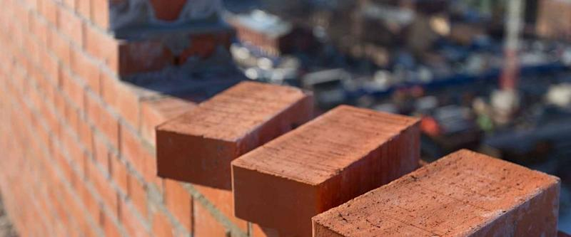Brickwork in the new house with three bricks in the foreground