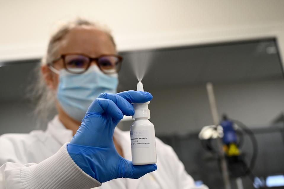 A laboratory worker tests a nasal spray at the Pharma and Beauty factory in Saint-Chamas, southeastern France, on January 21, 2021. - The Pharma and Beauty company has developped a nasal spray based on ionised water, known for its antimicrobial properties, which eliminates 99% of the viral load. (Photo by NICOLAS TUCAT / AFP) (Photo by NICOLAS TUCAT/AFP via Getty Images)