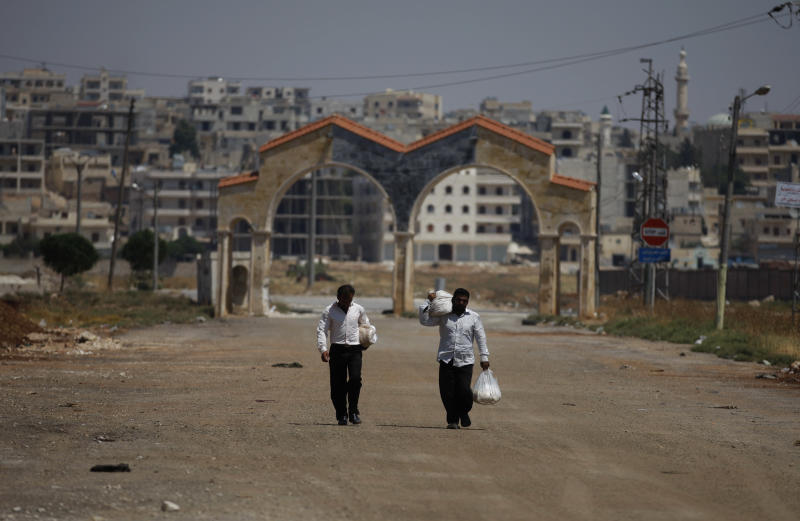 Syrians walk on a street at the entrance to the town of Anadan on the outskirts of Aleppo, Syria, Monday, Aug. 6, 2012. (AP Photo)