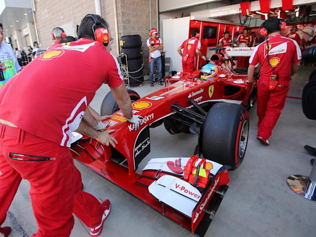 Ferrari mechanics push their driver Fernando Alonso of Spain's car back into their team garage during the second practice session for the Korean Formula One Grand Prix at the Korean International Circuit in Yeongam, South Korea, Friday, Oct. 4, 2013.(AP Photo/Aaron Favila)