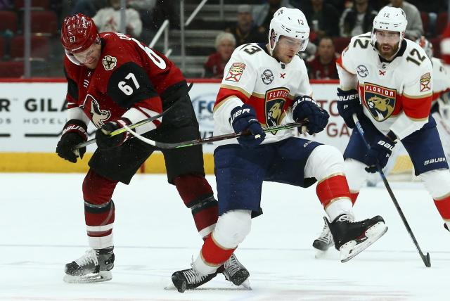 Arizona Coyotes left wing Lawson Crouse (67) competes with Florida Panthers defenseman Mark Pysyk (13) for the puck as Panthers defenseman Ian McCoshen (12) watches during the first period of an NHL hockey game Tuesday, Feb. 26, 2019, in Glendale, Ariz. (AP Photo/Ross D. Franklin)