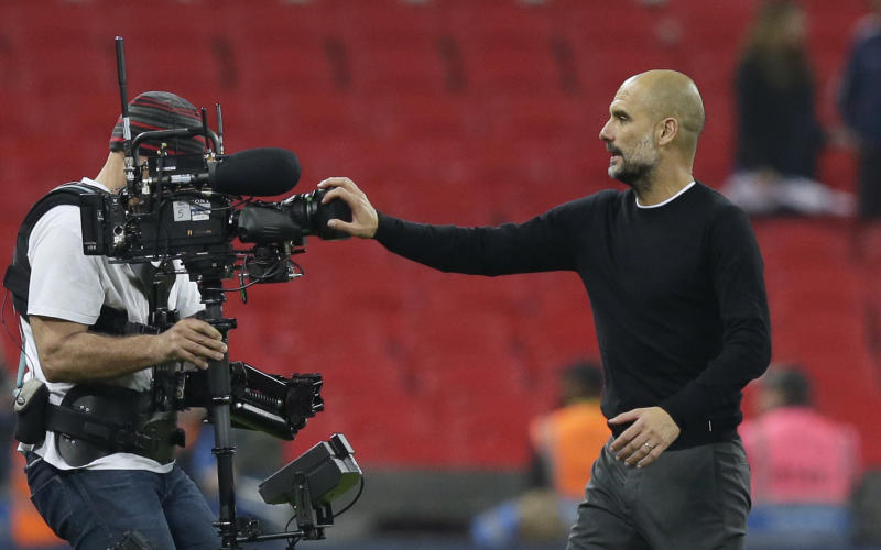 Manchester City coach Pep Guardiola covers a video camera with his hand as he leaves the field at the end of the English Premier League soccer match between Tottenham Hotspur and Manchester City at Wembley stadium in London, England, Saturday, April 14, 2018. Manchester City won 3-1. (AP Photo/Tim Ireland)
