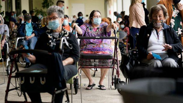 PHOTO: Resident Sabeth Ramirez, 80, center, waits in line with others for the Pfizer-BioNTech COVID-19 vaccine at the The Palace assisted living facility in Coral Gables, Fla., Jan. 12, 2021. (Lynne Sladky/AP)
