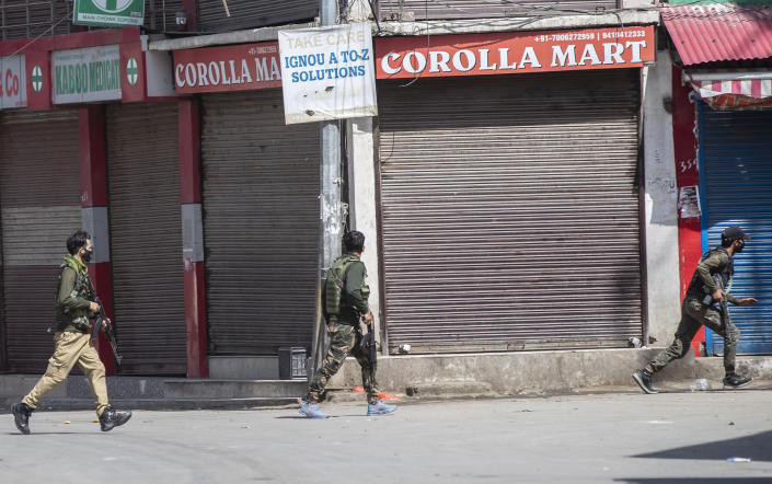 Policemen run near the site of a shootout at Sopore, 55 kilometers (34 miles) north of Srinagar, Indian controlled Kashmir, Saturday, June 12, 2021. Two civilians and two police officials were killed in an armed clash in Indian-controlled Kashmir on Saturday, police said, triggering anti-India protests who accused the police of targeting the civilians. (AP Photo/Mukhtar Khan)
