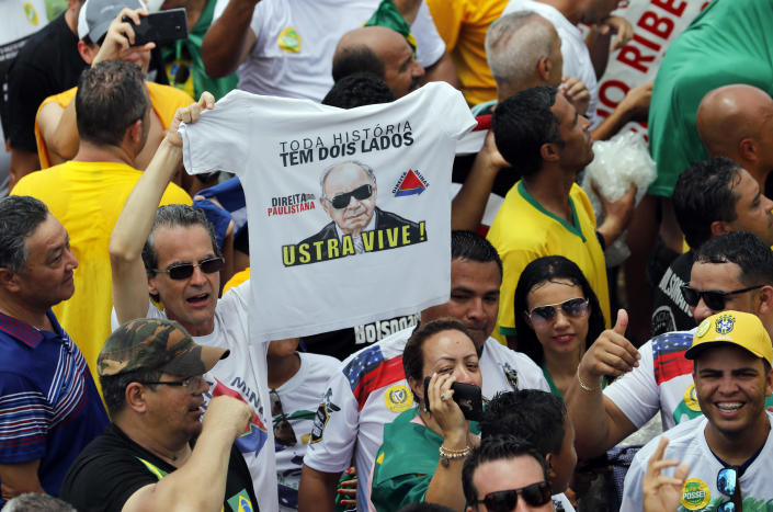 A supporter of Brazil's President Elect Jair Bolsonaro holds a T-shirt with the image of former army officer and right wing politician Carlos Alberto Brilhante Ustra, prior Bolsonaro's inauguration, in Brasilia, Brazil, Tuesday Jan. 1, 2019. Ustra, who died in 2015, became the first military official to be recognized, by a civil court in Sao Paulo, as a torturer during the military dictatorship. (AP Photo/Silvia Izquierdo)