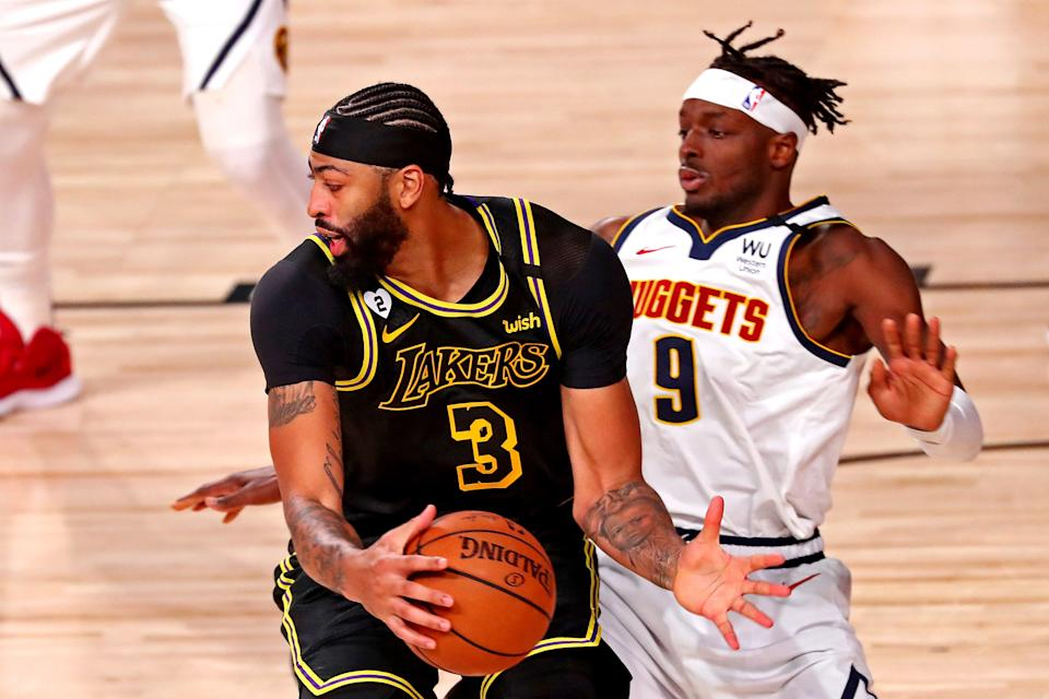 Los Angeles Lakers forward Anthony Davis handles the ball against Denver Nuggets forward Jerami Grant during Game 2 of the West finals Sept. 20, 2020 in Lake Buena Vista, Fla.