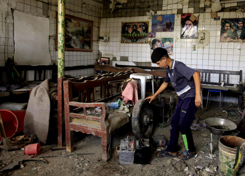 An Iraqi boy inspects damages at a cafe after a car bomb attack outside Kut, 100 miles (160 kilometers) southeast of Baghdad, Iraq, Sunday, Jun 16, 2013. Most of the car bombs hit Shiite-majority areas and were the cause of most of the casualties, killing tens. The blasts hit half a dozen cities and towns in the south and center of the country. (AP Photo/Karim Kadim)