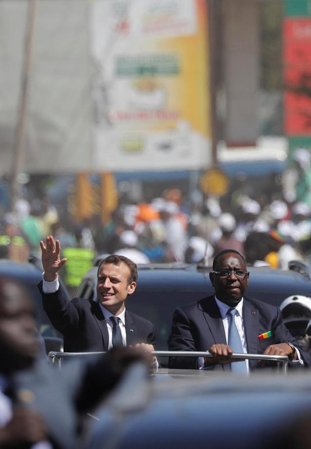 Senegalese President Macky Sall and French President Emmanuel Macron wave as they drive in Dakar, Senegal, after the inauguration of a school, February 2, 2018. REUTERS/Philippe Wojazer