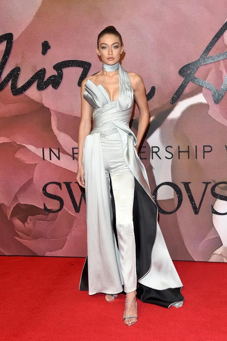 <p>The supermodel wore a stunning one-shoulder silver jumpsuit that tied at the neck. The ensemble featured pants and a train, because no girl should ever have to decide between the two. Hadid completed the look with a high bun, silver strappy heels, and heavy eye makeup. (Photo: Getty Images) </p>