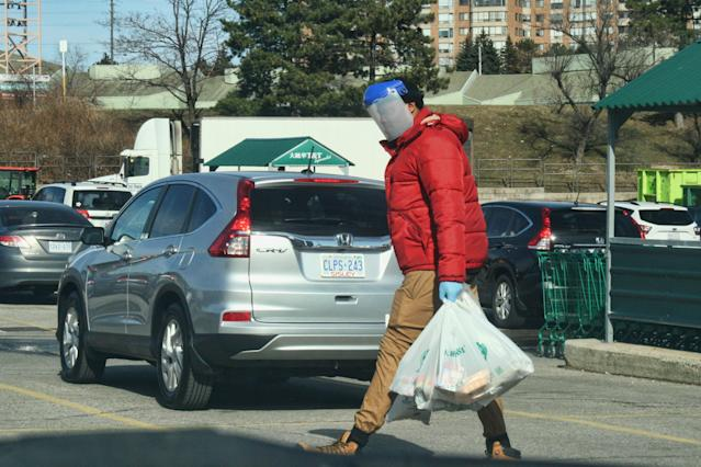 Man wearing a plastic face-shield and surgical gloves to protect him from the novel coronavirus (COVID-19) as he carries groceries in Toronto, Ontario, Canada on March 21, 2020. (Photo by Creative Touch Imaging Ltd./NurPhoto via Getty Images)