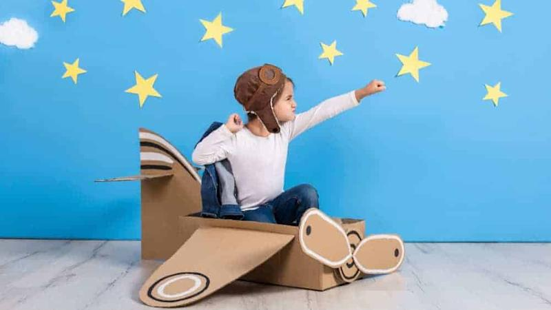 little girl in pilot costume playing and dreaming of flying over the sky