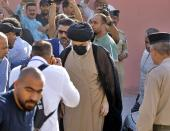 Populist Shiite cleric Muqtada al-Sadr, center, arrives to a polling center to vote in the parliamentary elections in Najaf, Iraq, Sunday, Oct. 10, 2021. Iraq closed its airspace and land border crossings on Sunday as voters headed to the polls to elect a parliament that many hope will deliver much needed reforms after decades of conflict and mismanagement. (AP Photo/Anmar Khalil)