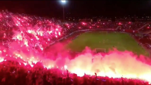 Algerian soccer fans filled a stadium in fire and red smoke. (Twitter)