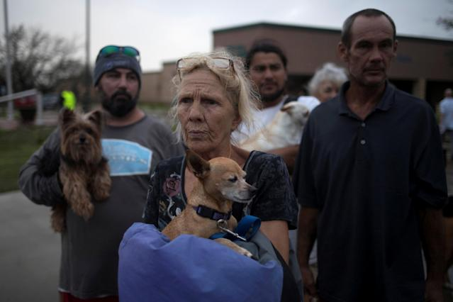 Julie holds her dog, Pee-wee, as they wait to be evacuated to Austin after losing their home to Hurricane Harvey in Rockport, Texas, Aug. 26, 2017. Adrees Latif/Reuters