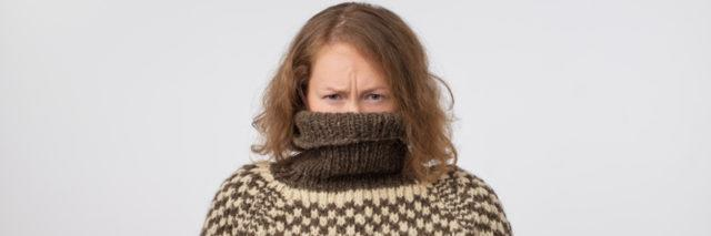 woman in brown and pale turtleneck with her face buried in the sweater looking at the camera