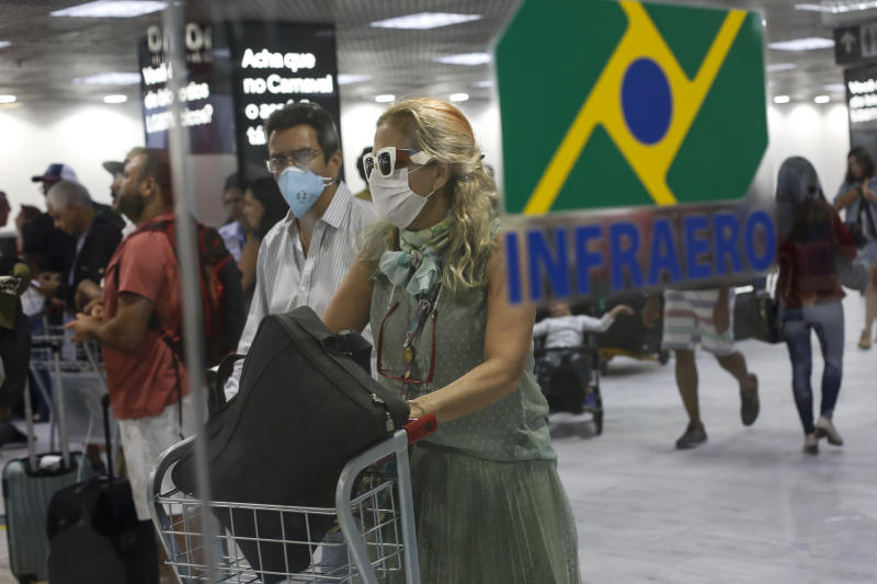 RIO DE JANEIRO, BRAZIL - MARCH 13: Passengers walk with their luggages wearing protective masks at Santos Dumont Airport on March 13, 2020 in Rio de Janeiro, Brazil. According to the Ministry of Health, Brazil confirmed 98 cases of coronavirus (COVID-19). (Photo by Bruna Prado/Getty Images)