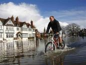 A resident cycles through deep water after the river Thames flooded the village of Datchet, southern England February 10, 2014. REUTERS/Eddie Keogh