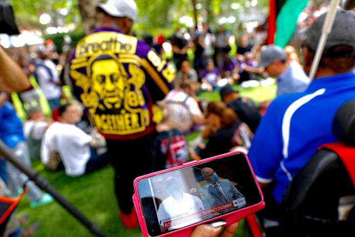 People watch the sentencing hearing of former Minneapolis Police officer Derek Chauvin outside the Hennepin County Government Center in Minneapolis on June 25, 2021.