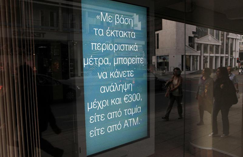 "A sign at a branch of bank of Cyprus reading in Greek, ""In light of the emergency restrictive measures, you can withdraw up to 300 euro either from the tellers or the ATM"", as people are reflected on the glass in central capital Nicosia, Cyprus, on Surtaday, March 30, 2013. Big depositors at Cyprus' largest bank may be forced to accept losses of up to 60 percent, far more than initially estimated under the European rescue package to save the country from bankruptcy, officials said Saturday. (AP Photo/Petros Karadjias)"