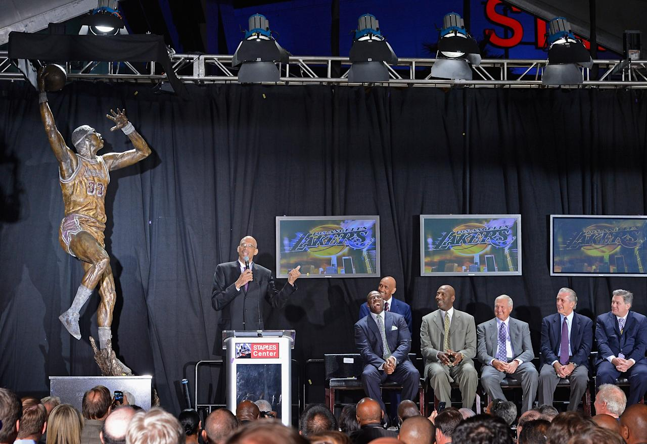 """LOS ANGELES, CA - NOVEMBER 16: Los Angeles Lakers legend Kareem Abdul-Jabbar (L) speaks after unveiling a statue of himself at Staples Center before the Lakers take on the Phoenix Suns on November 16, 2012 in Los Angeles, California. Looking on are as his former teammates Earvin """"Magic"""" Johnson (2ndL) James Worthy (3rdL) former Lakers general manager Jerry West, former Lakers coach Pat Riley(2ndR) and AEG president and CEO Tim Leiweke(Photo by Kevork Djansezian/Getty Images)"""