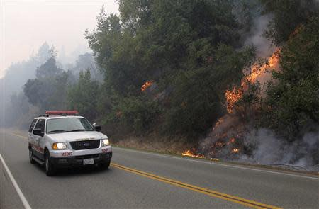 A wildfire burns next to Highway 1 in Big Sur, California, December 18, 2013. REUTERS/Michael Fiala