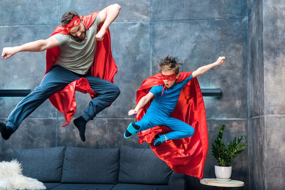 father and son in superhero costumes jumping on sofa at home (Photo: LightFieldStudios via Getty Images)