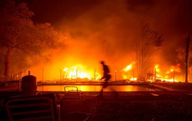 <p>A firefighter walks near a pool as a neighboring home burns in the Napa wine region in Calif. on Oct. 9, 2017, as multiple wind-driven fires continue to whip through the region. (Photo: Josh Edelson/AFP/Getty Images) </p>