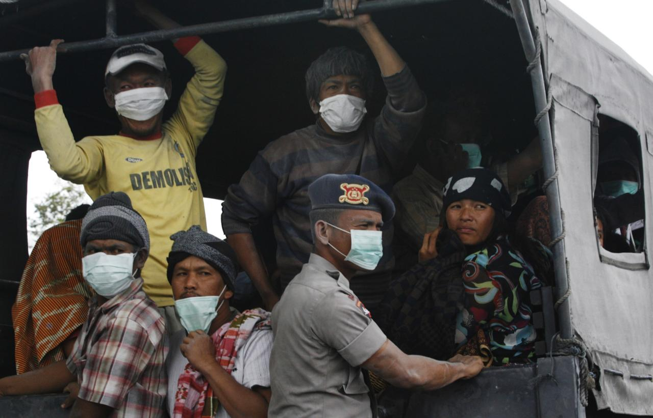 Villagers covered in ash sit on a truck while waiting to be evacuated to safety, as Mount Sinabung spews ash and hot lava during an eruption in Perteguhan village in Karo district, Indonesia's north Sumatra province, September 17, 2013. Mount Sinabung threw more volcanic ash into air, covering the surrounding areas on Tuesday, as authorities prepared more temporary shelters for evacuees. REUTERS/Tarmizy Harva (INDONESIA - Tags: DISASTER ENVIRONMENT)
