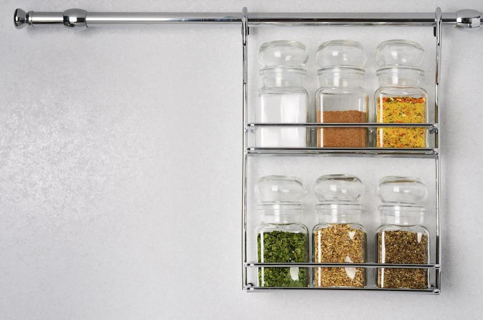 Bottles with spices and seasonings hanging on rack against white background