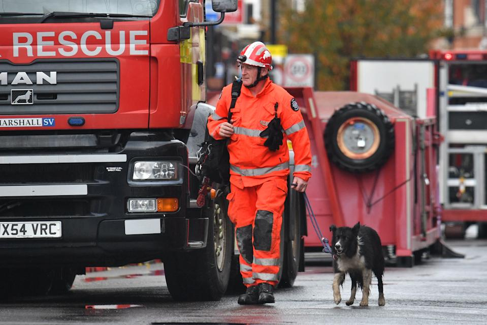 "Emergency services arrive with a dog at the scene of a suspected gas explosion on King Street in Ealing, west London. Rescuers are involved in a ""complex"" search for anyone who may still be inside the collapsed building."