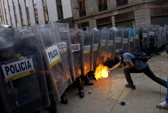 A demonstrator lights up a spray next to riot police in Mexico City, Saturday Dec. 1, 2012. Protesters opposed to newly sworn-in Mexican President Enrique Pena Nieto clashed with tear gas-wielding police early Saturday near the National Congress, where Pena Nieto took the oath of office. (AP Photo/Eduardo Verdugo)