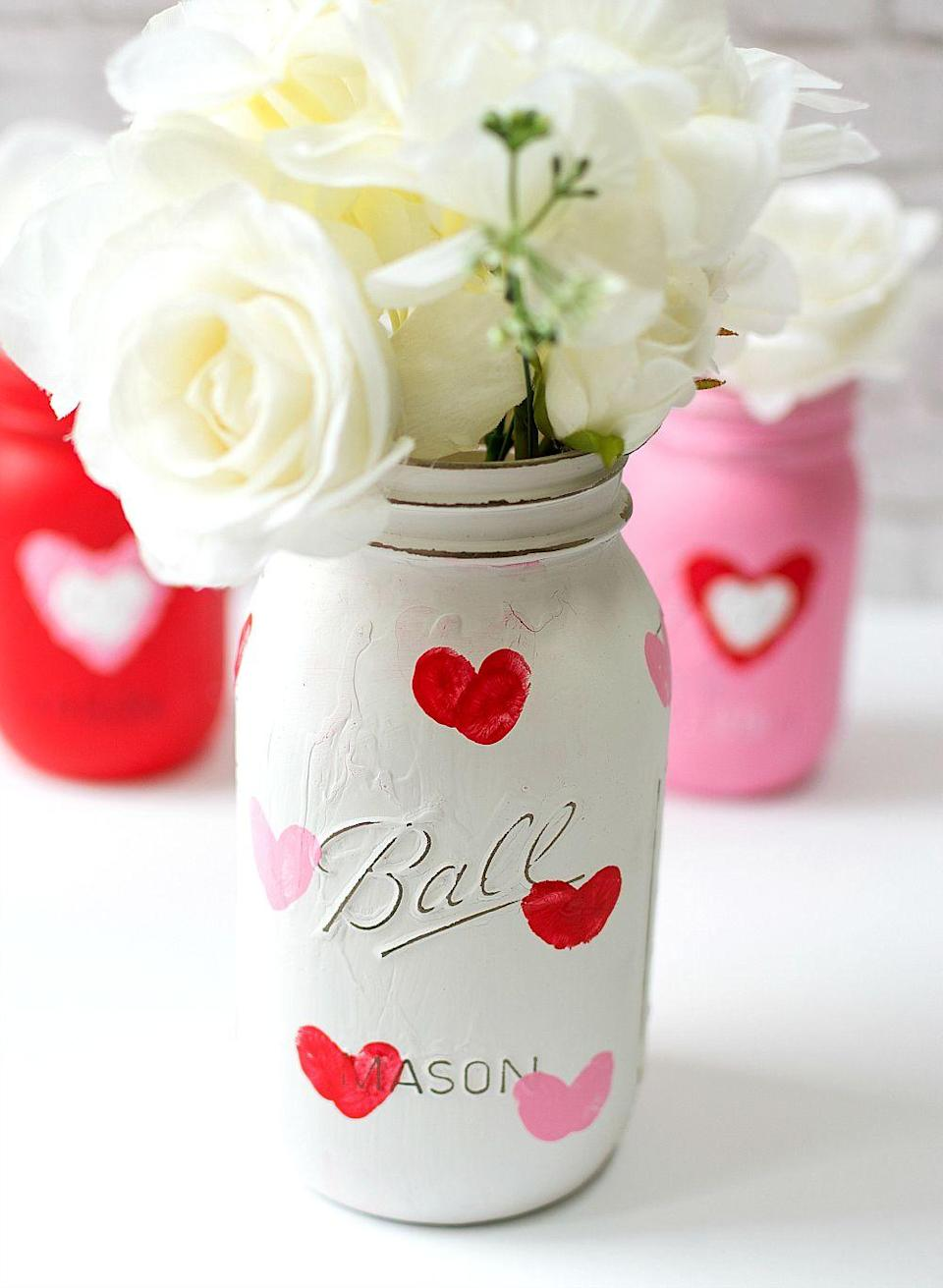 """<p>Use thumbprint hearts to add whimsy and color to mason jars, and turn them into cheerful vases for those holiday bouquets. Sand with sandpaper for a rustic look before sealing.</p><p><em><a href=""""https://www.itallstartedwithpaint.com/valentine-kid-craft-thumbprint-heart-jars/?"""" rel=""""nofollow noopener"""" target=""""_blank"""" data-ylk=""""slk:It All Started With Paint »"""" class=""""link rapid-noclick-resp""""><em>It All Started With Paint »</em></a></em></p>"""