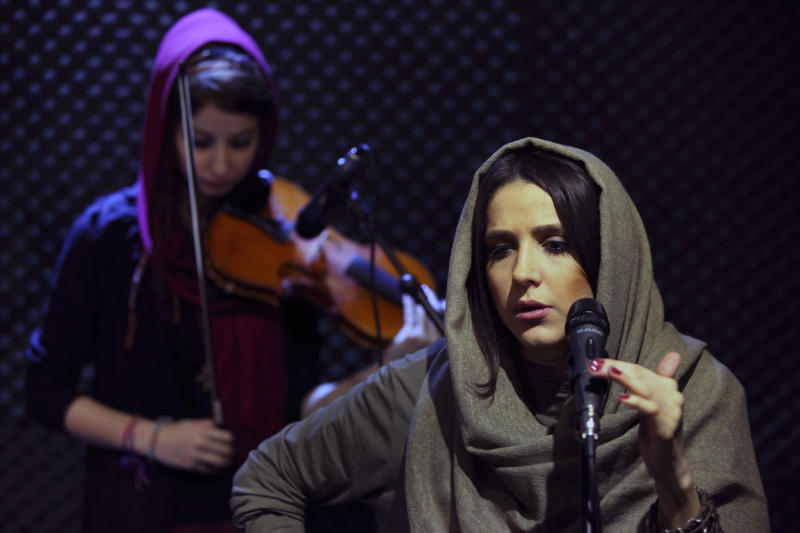 """In this picture taken on Friday, Jan. 25, 2013, female Iranian back vocalist Azadeh Ettehad and violinist Nastaran Ghaffari, both members of a band called """"Accolade,"""" perform in an unauthorized stage performance in Tehran, Iran. Headphone-wearing disc jockeys mixing beats. It's an underground music scene that is flourishing in Iran, despite government restrictions. (AP Photo/Vahid Salemi)"""