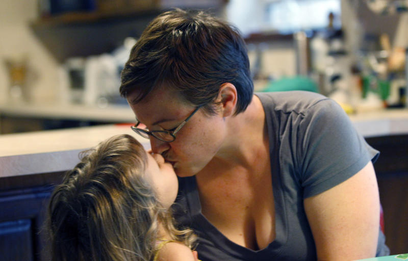 In this March 8, 2012 photo, Alexis Lohse, right, kisses her daughter Emma Miller, 3, at their home in Fort Worth, Texas. When Lohse decided to go back to college, the mother of two was so worried about health insurance that she didn't quit her job until finding the Women's Health Program. Texas Gov. Rick Perry is directing state officials to begin looking for money to keep the Medicaid Women's Health Program operating, even if the Obama administration revokes federal funding amid a fight over clinics affiliated with abortion providers. (AP Photo/LM Otero)