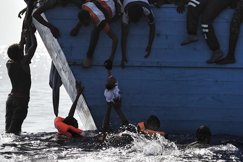 TOPSHOT - Migrants try to pull a child out of the water as they wait to be rescued by members of Proactiva Open Arms NGO in the Mediterranean sea, some 12 nautical miles north of Libya, on October 4, 2016. At least 1,800 migrants were rescued off the Libyan coast, the Italian coastguard announced, adding that similar operations were underway around 15 other overloaded vessels. / AFP / ARIS MESSINIS (Photo credit should read ARIS MESSINIS/AFP/Getty Images)