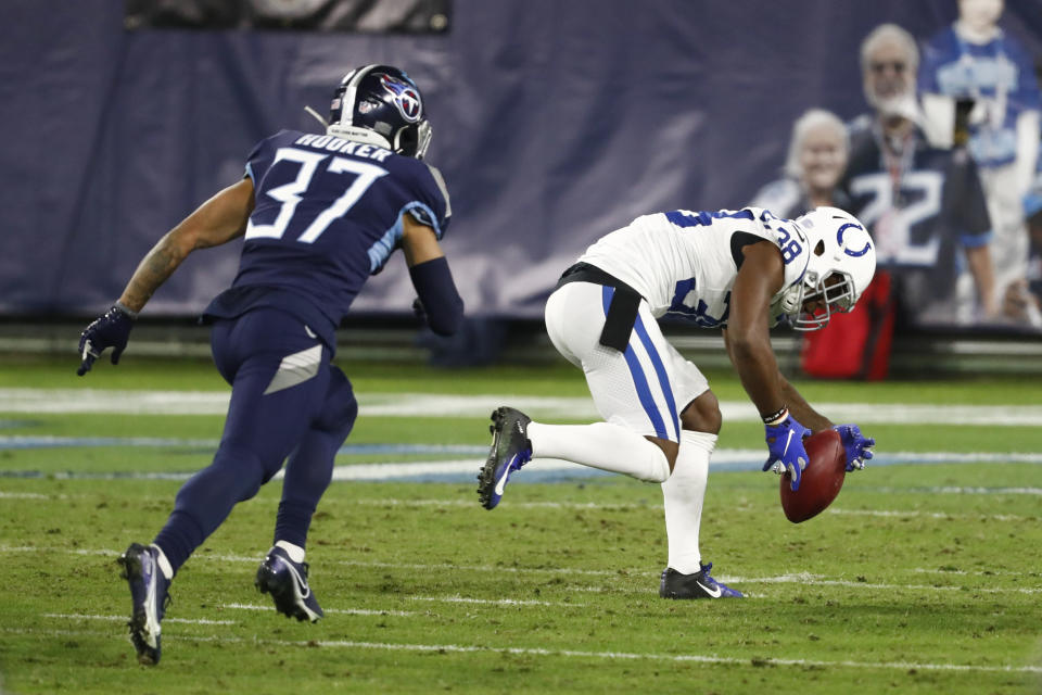 Indianapolis Colts cornerback T.J. Carrie (38) picks up a blocked punt ahead of Tennessee Titans safety Amani Hooker (37) and runs it back for a touchdown in the second half of an NFL football game Thursday, Nov. 12, 2020, in Nashville, Tenn. (AP Photo/Wade Payne)