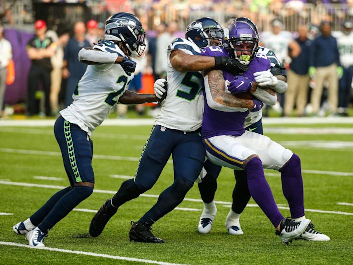 Tyler Conklin fights through tackles against the Seahawks.