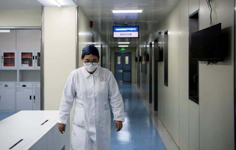 A nurse walks inside finished but still unused building A2 of the Shanghai Public Clinical Center Shanghai, following the outbreak of the new coronavirus, in Shanghai