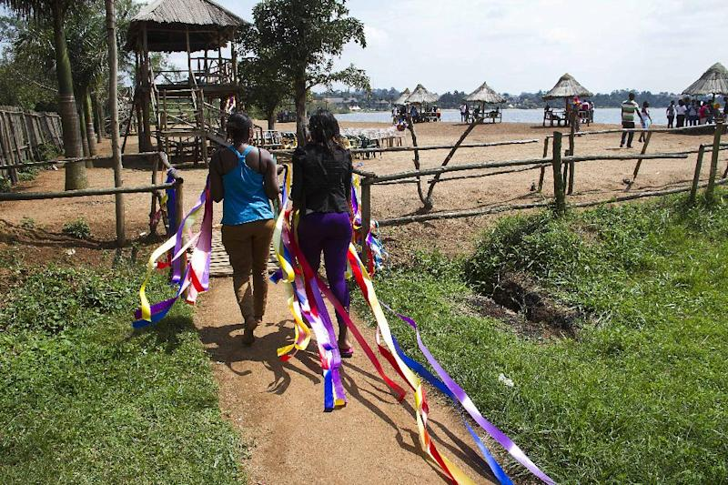 Ugandan activists hold colorful garlands as they take part in a gay-pride march in Entebbe, on August 9, 2014 (AFP Photo/ISAAC KASAMANI)
