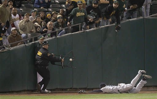 A security guard moves a chair from the path of Seattle Mariners center fielder Trayvon Robinson, right, who cannot make the catch on a ball hit in foul territory by Oakland Athletics' Coco Crisp in the fifth inning of a baseball game Friday, Sept. 28, 2012, in Oakland, Calif. (AP Photo/Ben Margot)